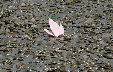 A folded paper crane, a symbol of hope, is placed on coins which are collected for undernourished children in Seoul