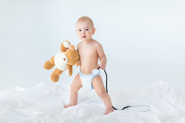 Adorable small baby boy standing on bed and holding stethoscope with teddy bear, 1 year old baby concept