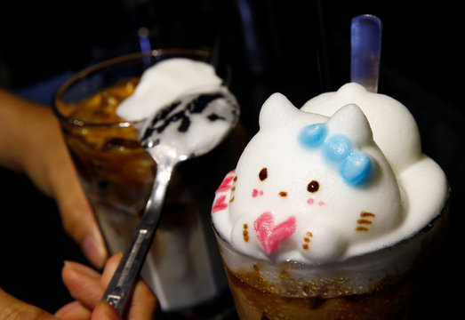 A barista creates a Hello Kitty 3D latte art on a cup of iced coffee at a cafe in Singapore