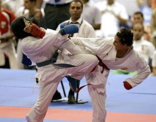 Aljou Ilhem of Algeria kicks Chaima Madjdi of Egypt during karate match at the All Africa Games in Algiers