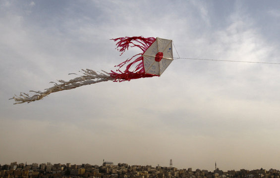 Kite depicting Japanese flag, released by members of the Follow Women Foundation, flies in air at Amman Citadel