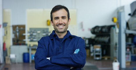 Portrait of a young beautiful car mechanic in a car workshop, in the background of a car service Concept repair of machines, fault diagnosis, repair specialist, technical maintenance on-board computer