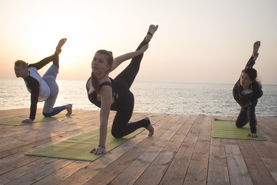 Group of fit womans and man doing yoga in morning on the beach
