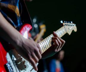 Mani suonano chitarra elettrica, fuoco selettivo