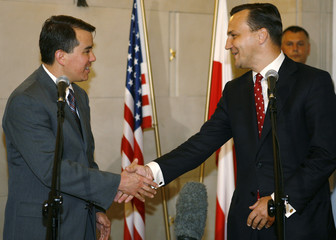 U.S. chief negotiator Rood shakes hands with Polish Foreign Minister Sikorski after their missile shield preliminary deal was signed in Warsaw