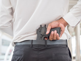 Businessman on a white shirt hide the gun on his back side waistband pant