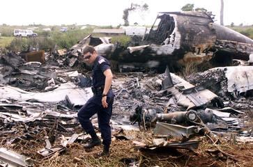 A UN INVESTIGATOR SEARCHES THROUGH WRECKAGE OF PLANE CRASH IN EASTTIMOR.