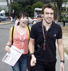 A fan screams with excitement after Renault Formula One driver Fernando Alonso of Spain signed autographs for her as he arrives at the pits before the start of the first practice session of the Singapore F1 Grand Prix at the Marina Bay street circuit