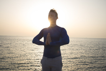 Portrait of young man meditating on the beach, sunrise background