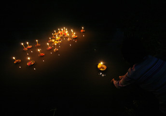 A villager prays before floating a kratong into a pond during the Loy Kratong festival in Nakhonsawan province