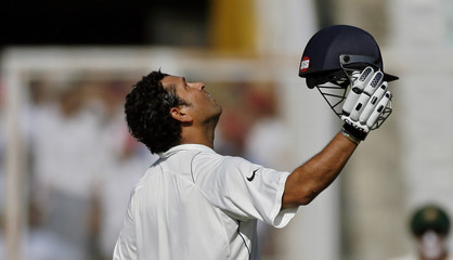 India's Tendulkar celebrates after becoming the highest test-run scorer on the first day of their second test cricket match against Australia in Mohali