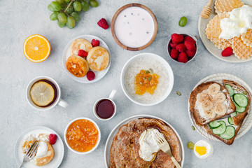 Morning atmosphere. Healthy breakfast with porridge, oatmeal, pancakes, lots of berries and snacks on blue rustic background.