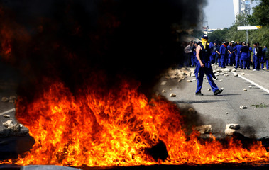 Delphi's workers protest behind a burning barricade in Puerto Real