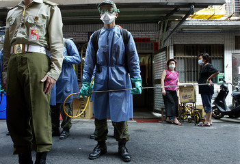 A TAIWAN SOLDIER WEARS CHEMICAL SUIT AS TWO WOMEN LOOK ON IN TAIPEI.