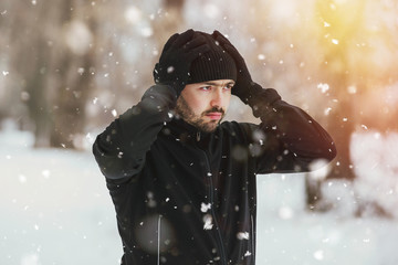 Itness, sport, people, healthy lifestyle concept - a young man with a beard preparing for a jog in the winter in the park