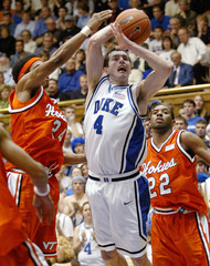 Duke University's Redick is fouled by Virginia Tech's Markus Sailes as he drives to the basket during their NCAA game in Durham