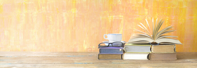 opened book, cup of coffee,specs, on grungy background, panoramic format