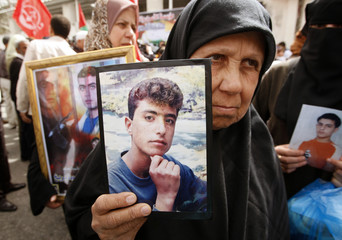 Palestinian women hold pictures of jailed relatives during a protest in Gaza