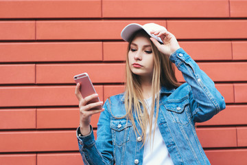 Stylish young blonde in a cap and denim jacket talking on the phone pink color on a red background. Young beautiful woman hipster use a mobile phone.