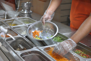 the cook puts pieces of vegetables for salad in a bowl. tray with assorted for salad in the window of a fast food restaurant