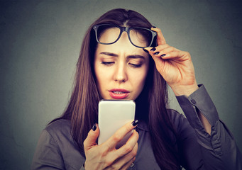 Woman with glasses having trouble seeing cell phone has vision problems.