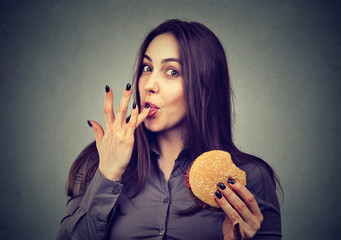 Fast food is my favorite. Young woman eating a hamburger enjoying the taste