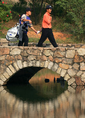 Liang Wenchong of China walks across a bridge during first round of China Open in Shenzhen, China
