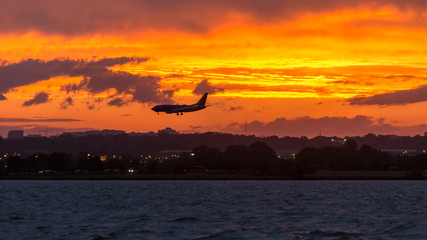 A Boeing 737 on short final into Reagan National Airport (DCA) as the sun sets over the Potomac River with storms and rain moving through the Washington, D.C. area