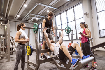 Group of people in gym training weight lifting