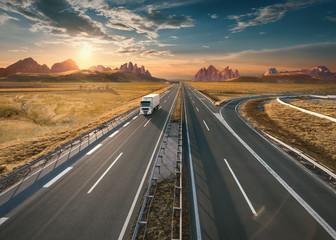 Lone white truck on highway at idyllic sunset