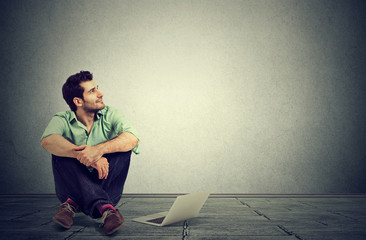 man with laptop computer sitting on a floor planning daydreaming