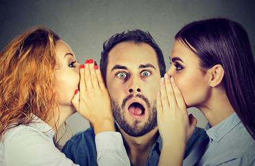 Two women telling whispering secret gossip in the ear to an amazed shocked man