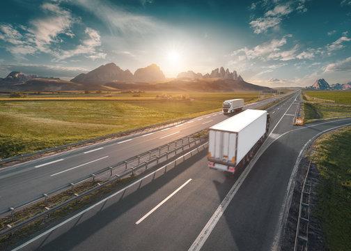 Two lone white trucks on highway at idyllic sunny morning