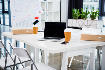 workplace with laptop, coffee paper cups in modern office