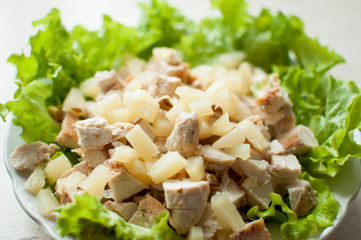 Hawaiian salad in the plate. Chopped ruddy chicken breasts with leaf salad, pieces of pineapple and crushed walnut.