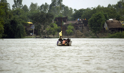 Villagers cross flooded river on boat in Ranigarh village