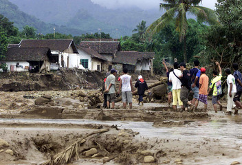 Indonesian villagers walk through mud after flood and landslides in village of Rambi Puji near town of Jember in East Java