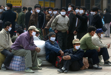 CHINESE TRAVELLERS WEAR MASKS TO WARD OFF SARS AS THEY WAIT FOR TRAINSAT A RAILWAY STATION OF BEIJING.