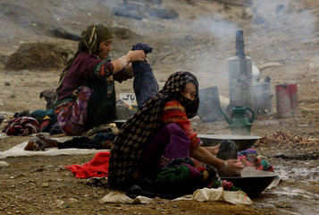 AFGHAN WOMEN WASH CLOTHES IN KABUL RIVER.