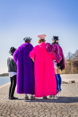 Caucasian men in colorful fake furs and hats standing on a city quay together and holding each other, seen from behind.