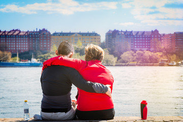 Love couple sitting close together in sunshine on a quay in central Stockholm Sweden, seen from behind. Water and cityscape in the background.