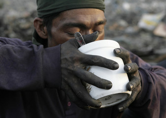 A charcoal maker drinks soup for breakfast at garbage dump where  hundreds of people live and make a living recycling waste and making charcoal in Tondo