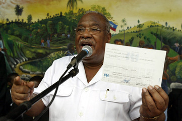 Haitian Prime Minister hands out checks to former soldiers.
