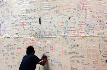 A volunteer writes his thoughts on message wall at a temple-morgue for tsunami victims in ...