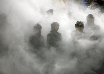 Egyptian policemen are shrouded in smoke as supporters of EST from Tunisia burn chairs during their African League Group B soccer match against Al Ahly in Cairo
