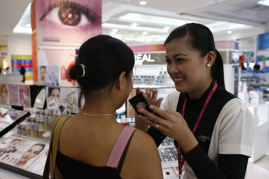 A sales girl for a cosmetic company applies make-up on a shopper in a department store in Makati City