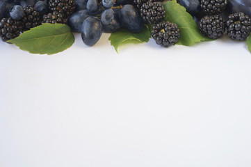 Group of fresh fruits and berries on a white background. Ripe blueberries, blackberries and grapes. Top view with copy space.