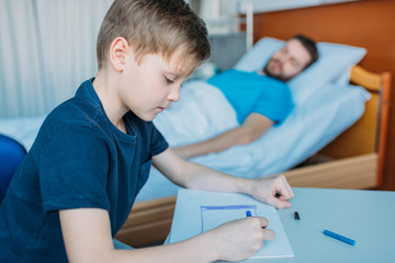 son drawing pictures while sick father laying on hospital bed at ward, dad and son