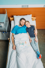 father with son embracing while laying on hospital bed at ward, dad and son