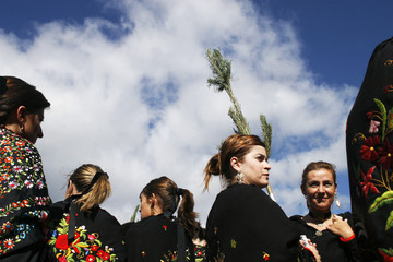 "Women dressed as ""pinorras"" carry pine branches as they wait for the start of a procession during the Pinochada festival in Vinuesa"